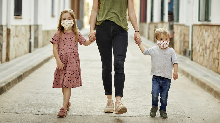 Mother with daughter and son, holding hands walking on the street, wearing home made face mask for coronavirus pandemic.