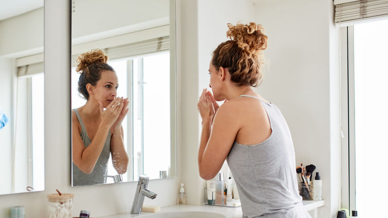Woman smelling her breath while looking in the mirror