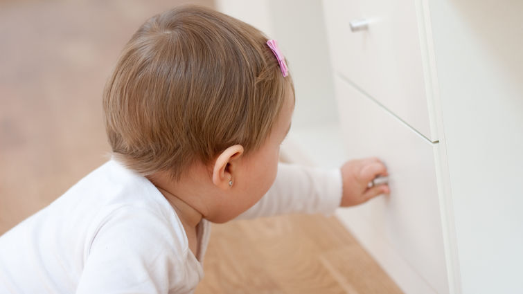 Baby girl opening a drawer with curiosity. Risks at home with little children.