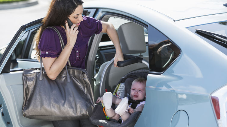 Young Hispanic woman (20s) traveling with baby girl (6 months), in car seat, talking on mobile phone.