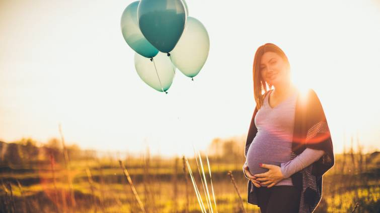 Pregnant woman standing in the middle of a field with balloons.