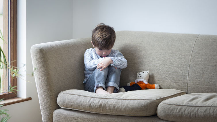 Little boy suffering from child abuse curled up on the sofa with his teddy.