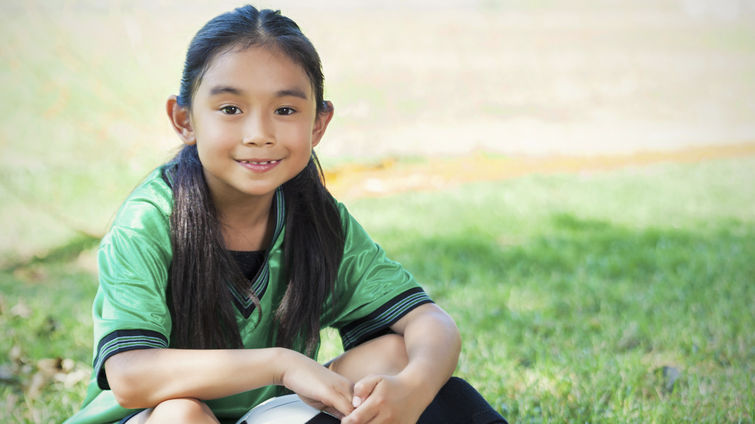 elementary age Hispanic female soccer player sits on the ground after her game. She is smiling big and holding a soccer ball. She has long brown hair and brown eyes. The playing field and soccer goal are in the background.