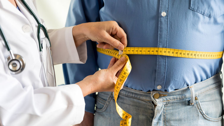 Obese man being measured by doctor