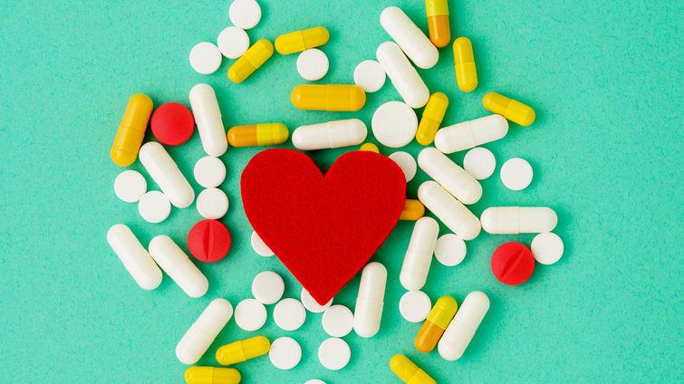Heart cutout on backdrop of medical pills