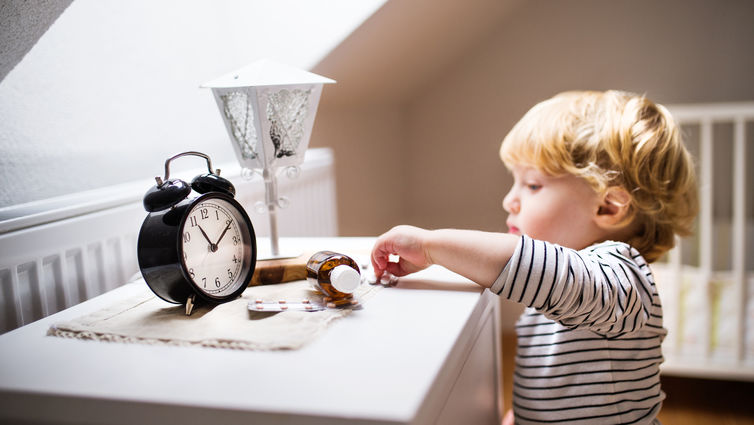 toddler boy reaching for pills on nightstand