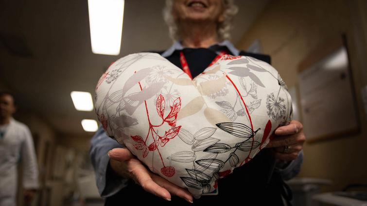 woman holds heart pillow