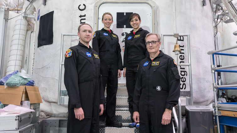 While at NASA, four volunteers stand in front of the simulated shuttle they participated in for. 45 days.
