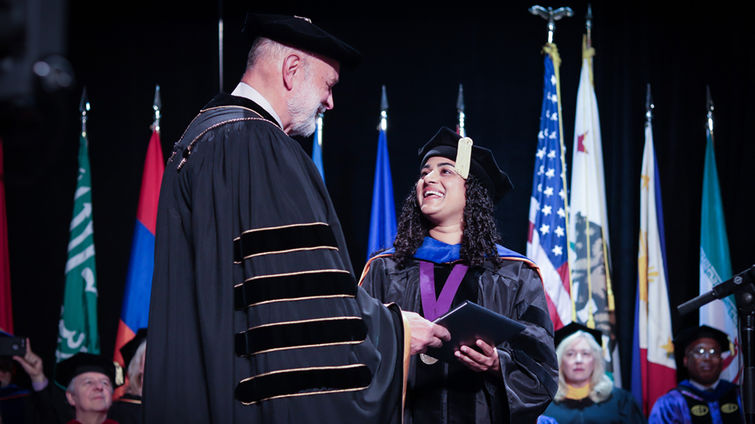Elsie Lobo accepts the LLU President's Award from Richard Hart during commencement