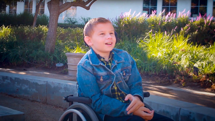 adolescent boy sitting outside in wheelchair