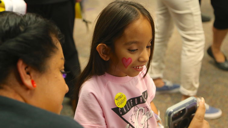 Loma Linda University Children's Hospital patient Jennifer Alvarado, 9, of Fontana, gets a closer look at her face paint during the Spirit Fall Festival on Thursday, Oct 18.