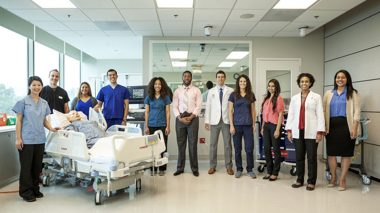 Loma Linda University staff of nurses, physicians and faculty stand in the middle of a patient's room.