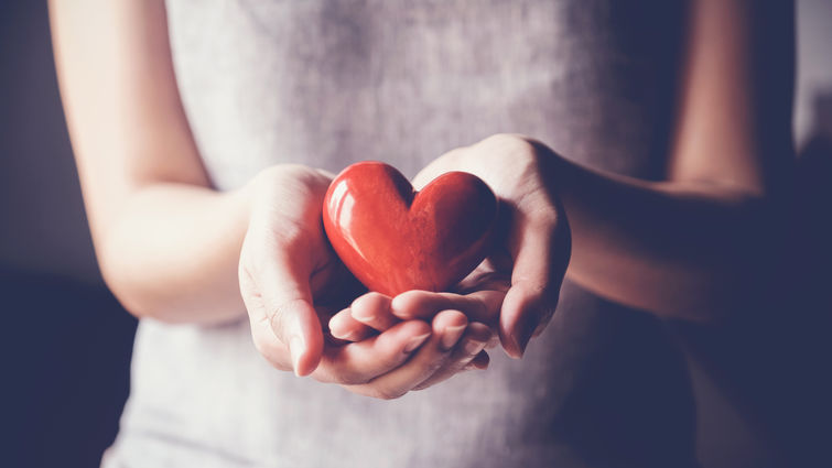 woman holding a heart shape in her hand