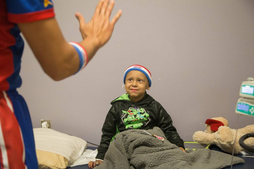 "Harlem Globetrotter ""Zeus"" McClurkin gives a young chemotherapy patient a head band and a high-five for encouragement. The Harlem Globetrotters brought Valentine's Day cheer to children at the Loma Linda University Children's Hospital Hematology/Oncology Clinic on Wednesday, February 14, 2018, in Loma Linda, California."