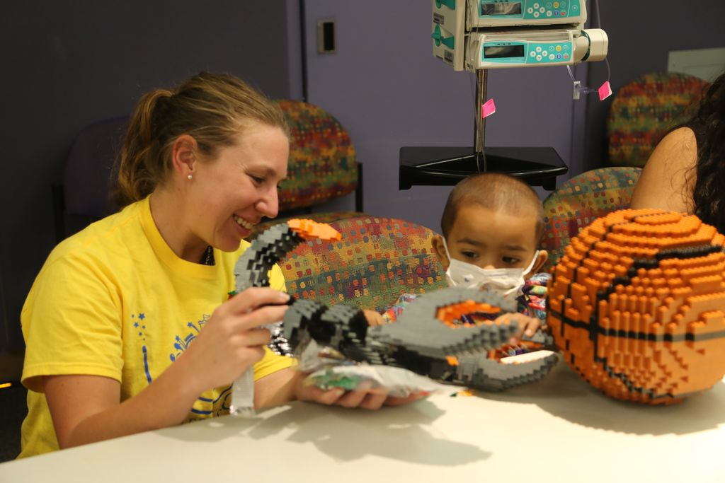 A team member of Merlin's Magic Wand interacts with a patient over legos