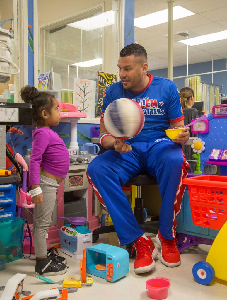 "Harlem Globetrotter ""El Gato"" Melendez shows young cancer patient a spinning ball trick. The Harlem Globetrotters brought Valentine's Day cheer to children at the Loma Linda University Children's Hospital Hematology/Oncology Clinic on Wednesday, February 14, 2018, in Loma Linda, California."