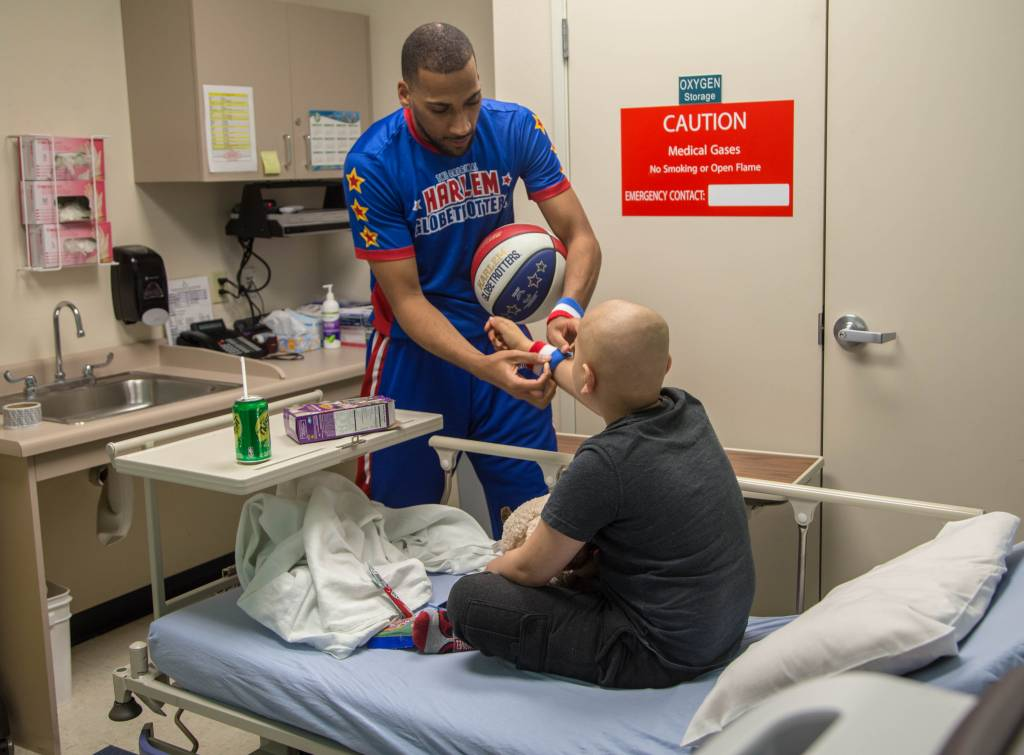 "Harlem Globetrotter ""Zeus"" McClurkin gives a young chemotherapy patient one of his wristbands for encouragement. The Harlem Globetrotters brought Valentine's Day cheer to children at the Loma Linda University Children's Hospital Hematology/Oncology Clinic on Wednesday, February 14, 2018, in Loma Linda, California."