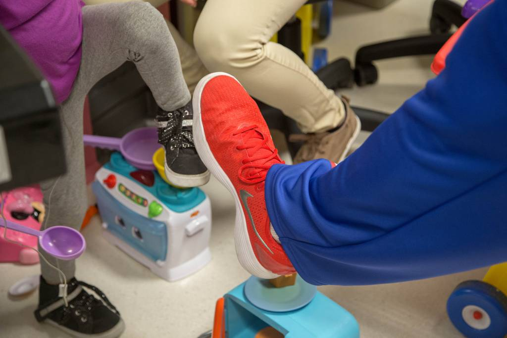 """Harlem Globetrotter """"El Gato"""" Melendez, 6'8"""", compares shoe sizes with a young patient. The Harlem Globetrotters brought Valentine's Day cheer to children at the Loma Linda University Children's Hospital Hematology/Oncology Clinic on Wednesday, February 14, 2018, in Loma Linda, California."""