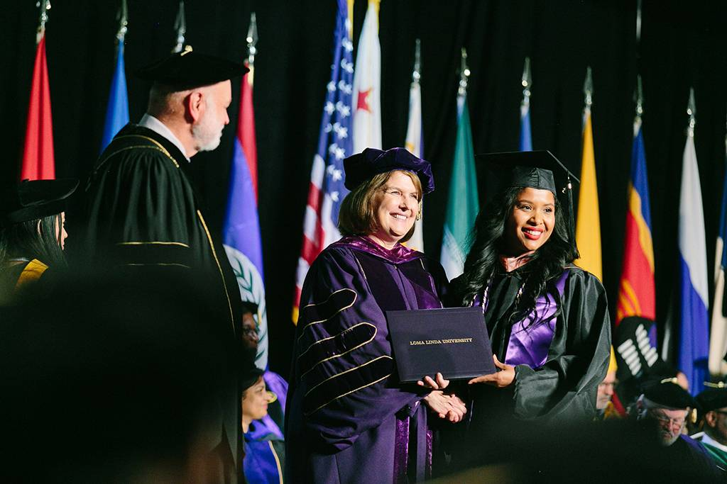 A graduate smiles as she receives her diploma from President Hart, Dean Marshak.