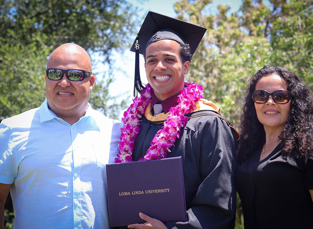 A graduate celebrates with his family at the end of a long educational pilgrimage.