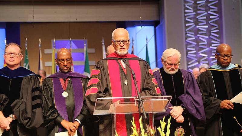Campus Chaplain Terry Swenson, DMin, MDiv, leads a prayer of dedication.