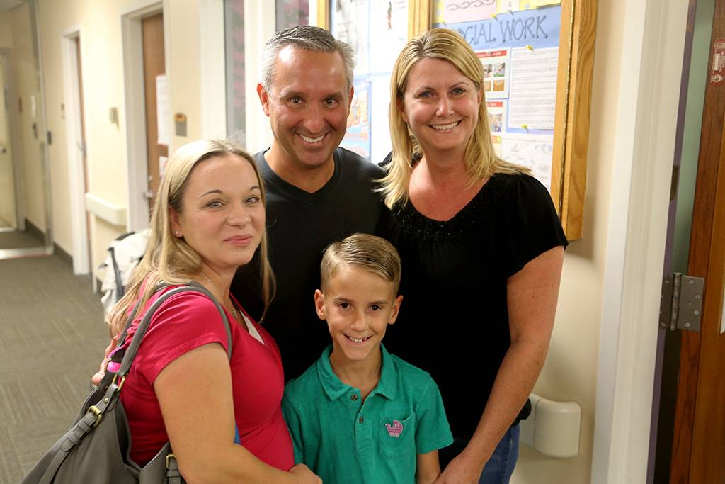 Connor Inderbitzen (center) joins his mom and dad, Erik and Vicki, and Jacey Steinmetz, one of the NICU nurses who cared for him at Loma Linda University Children's Hospital 12 years ago.