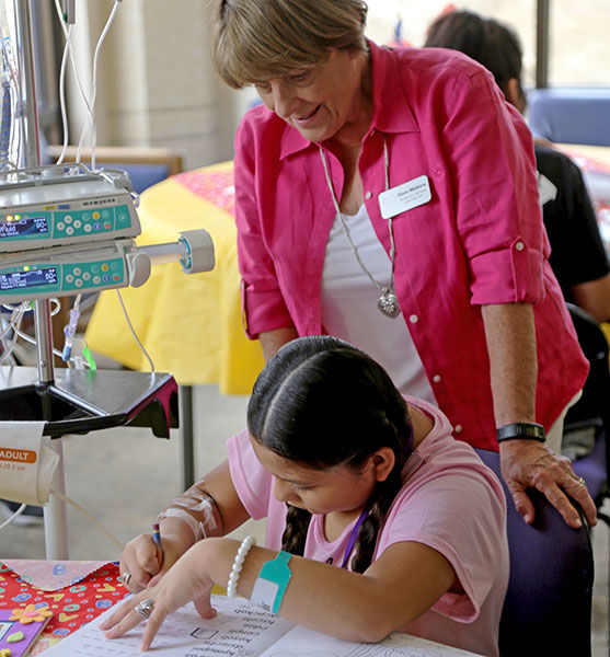 Dixie Watkins, co-president of the Big Hearts for Little Hearts Guild, assists a patient at Fall into Reading
