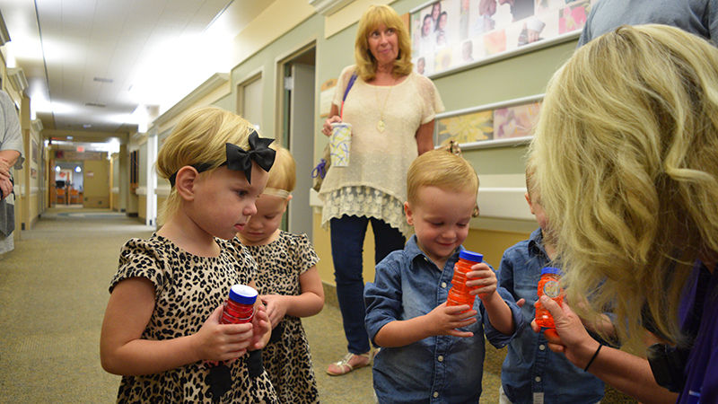 Courtney Martin, who helped care for Brittany during her pregnancy, hands out bubbles to the quadruplets—which became their focus for the rest of the visit.