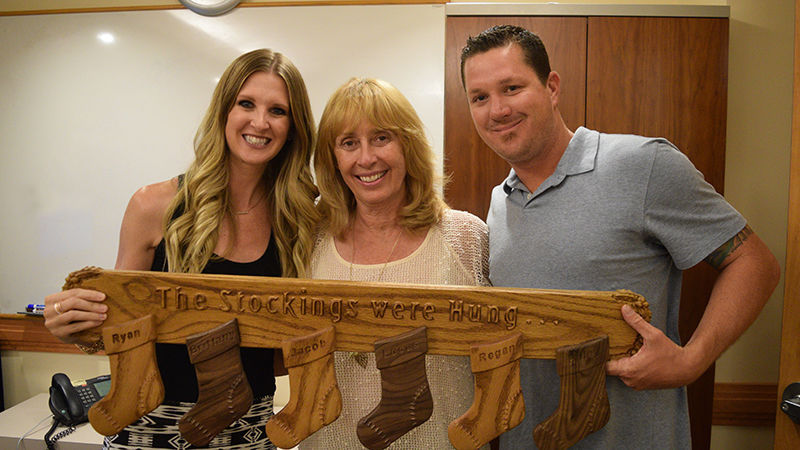 Brittany (left) and Ryan (right) accept a gift from night nurse Phyllis Zehmas, whose husband handcrafted it for the Stuit family.