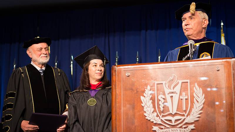 Flanked by President Richard Hart, MD, DrPH, and School of Religion Dean Jon Paulien, PhD, is an honored graduate.