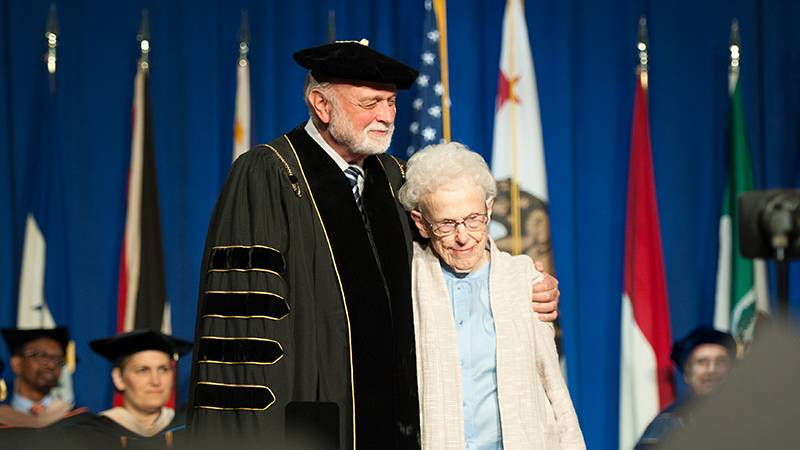 President Richard Hart, MD, DrPH, hugs legendary nurse Maxine Darling as she receives the Lifetime Service Award from the School of Nursing.