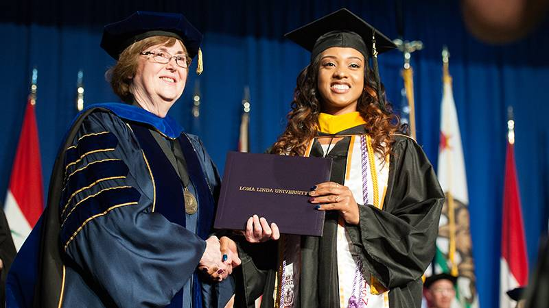 A School of Nursing graduate shares a handshake and smile with Dean Elizabeth Bossert, PhD.