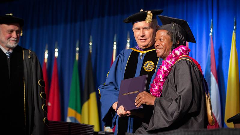 President Richard Hart, MD, DrPH, and Dean of the School of Religion Jon Pauline, PhD, share smiles with this graduate receiving his diploma.