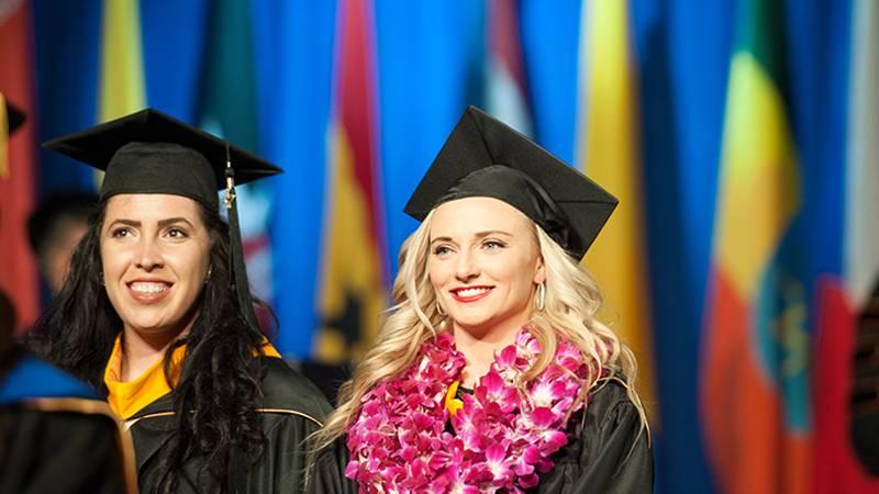 Two smiling nursing graduates
