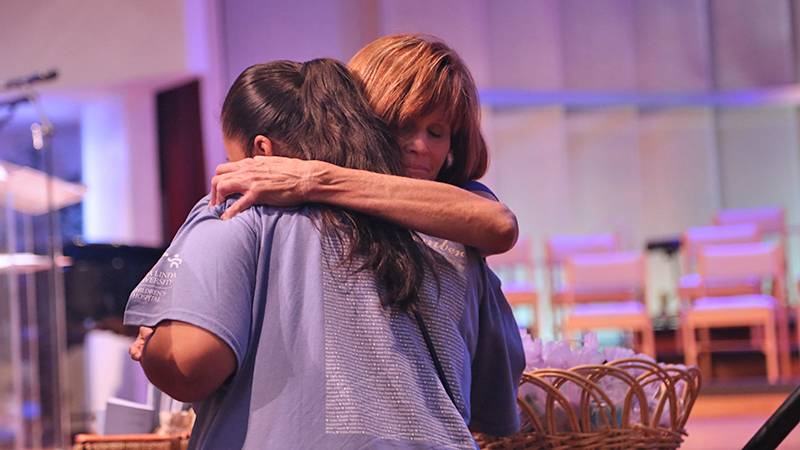 A mourning mother is comforted by Cathy Regan, MEd, child life specialist at Loma Linda University Children's Hospital.