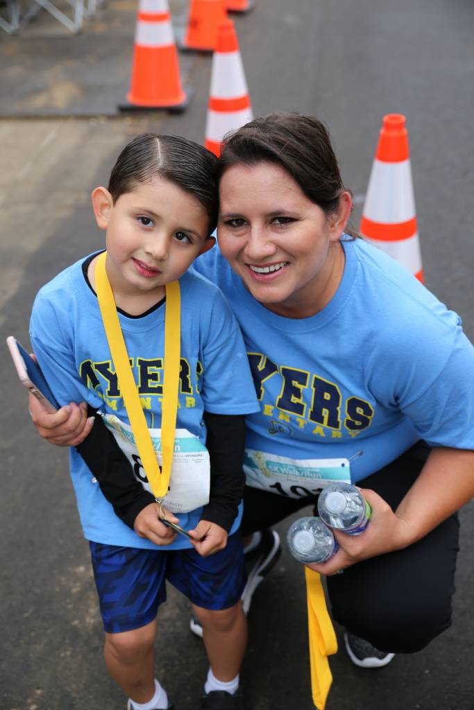 Two participants from Myers Elementary School's running club smile happily as they receive their medals and water. The Stand up to Stigma 5K raised funds for a new playground and brought awareness to mental health issues.
