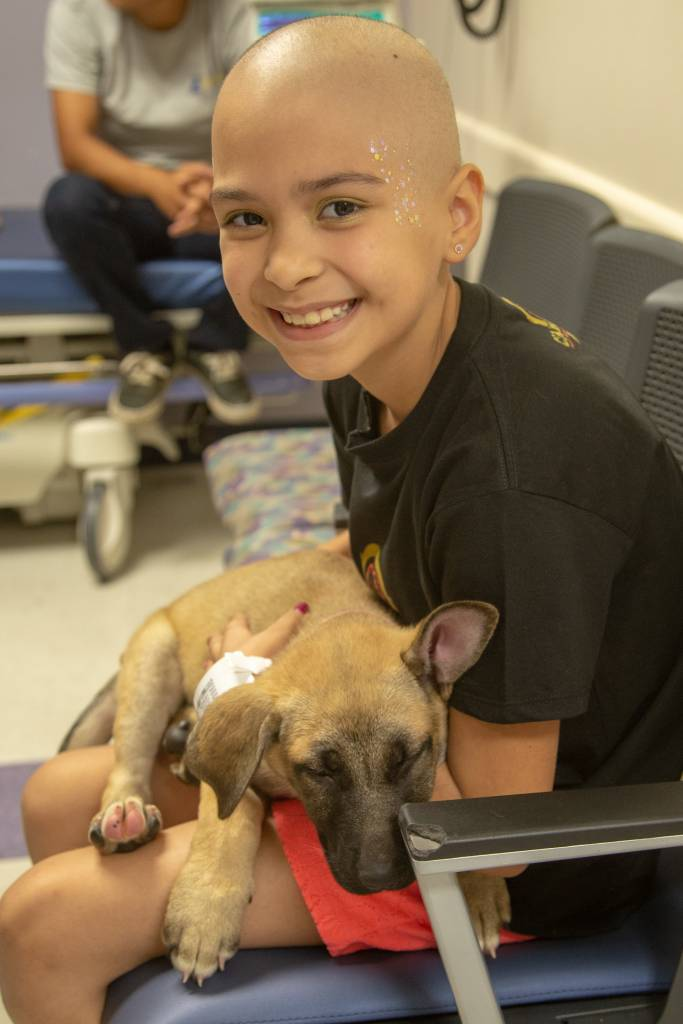 Caylee Cardenas, 9, from San Bernardino, cuddles up with one puppy.