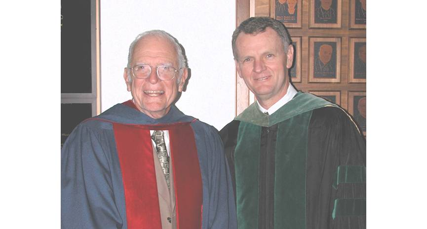 Louis Smith, MD, at left, received the University Distinguished Service Award in 2003 for starting organ transplantation at Loma Linda University Health and for mentoring generations of future doctors, including Roger Hadley, MD (right), dean of the School of Medicine. They are shown in academic regalia for the graduation ceremony in which Smith accepted his award.