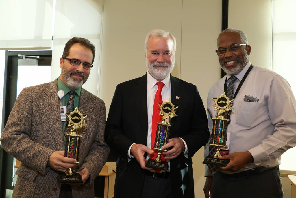 three men showing awards for No Shave LLUH