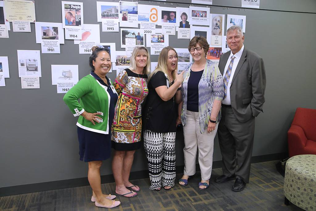Colleagues and friends of Carlene Drake gathered in front of a timeline that captures both advances in technology and milestones in Drake's life.