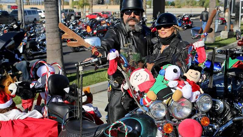 man and woman stand with decorated motorcycles