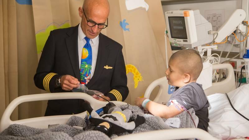male pilot visits with hospital patient