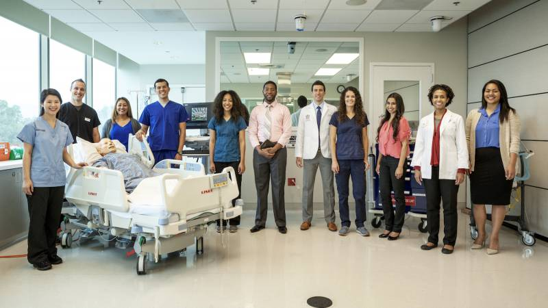 Group of Loma Linda University staff standing in the middle of a patient room.