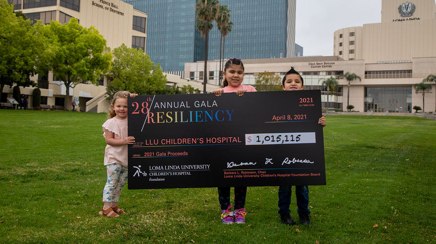 three kids standing in front of hospital with giant check
