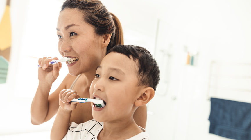 mom with son brushing teeth
