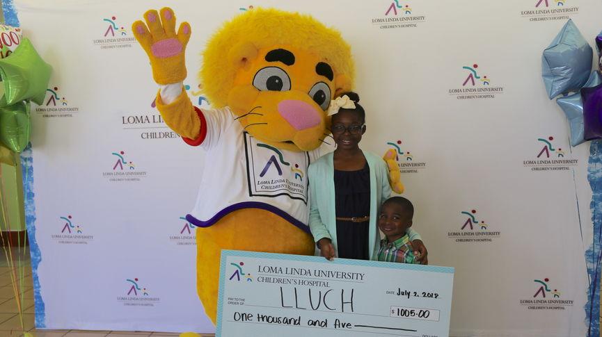 Alyssa and Ashton Jean-Marie presented a check to LLU Children's Hospital alongside mascot Luke the Lion on Monday, July 2.