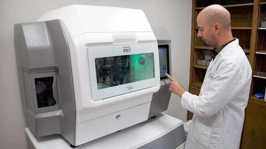 Technician stands at PM7 machine