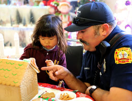Firefighter helps young girl decorate gingerbread house