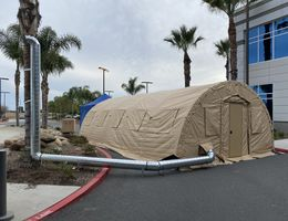 tan medical tent next to hospital