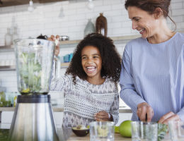 Little girl and woman making a smoothie